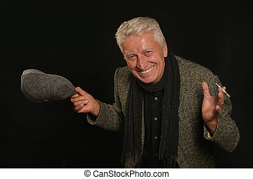 Smiling Senior man smoking cigarette over black background