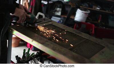 Grinding metal in home garage - Man Grinding metal in home...