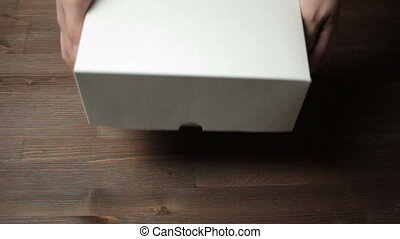 Hands opening a box of cupcakes.