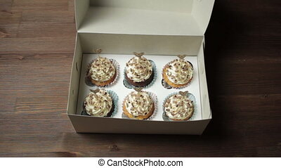 Hands close a box of cupcakes.