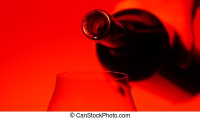 Red wine being poured into wineglass, red, slowmotion, closeup