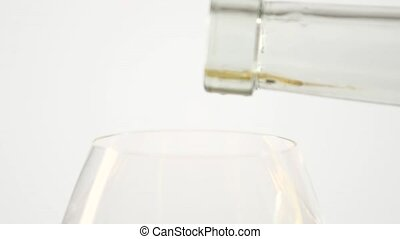 White wine pouring in a glass from a bottle, white, closeup, slowmotion
