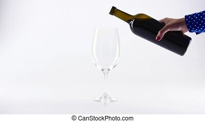 Glass of red wine in a female hand, on white background,...