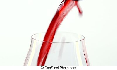 Red wine pouring into a glass, white, closeup