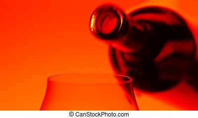 Red wine being poured from bottle to glass, orange, closeup...