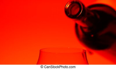 Red wine pouring in glass, red, closeup