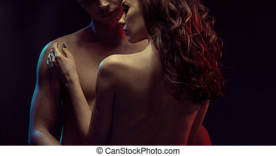 Portrait of two young lovers in dark bedroom