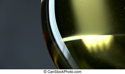 White wine being poured into a wineglass, grey, closeup,...