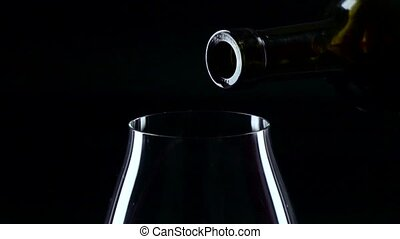 Bottle and glass with red wine, black, closeup, slowmotion -...