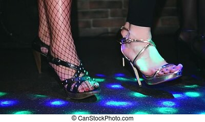 Woman feets on high heels synchronously tap on floor. Fashion show in nightclub.