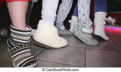 Woman feets in soft slippers synchronously rubs on floor. Party in nightclub.
