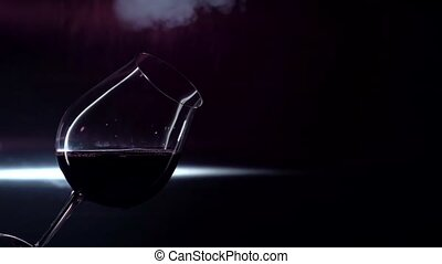 Smoking glass of red wine, black, backlights, slowmotion -...