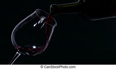 Red wine splash on a glass, black, slowmotion, closeup - Red...