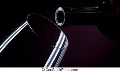 The bottle of wine, the wine is poured into a glass, black,...
