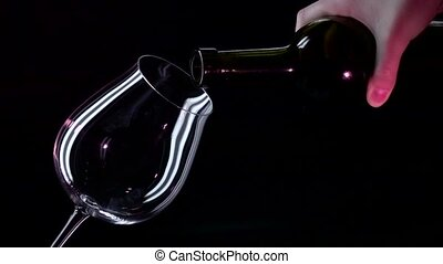 Bottle, glass with red wine, black, closeup, slowmotion