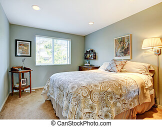 Modern guest bedroom with beige bedding, and carpet.
