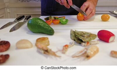 Cook's hands preparing salad, fresh avocado, fried scallops,...