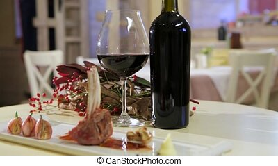 Luxury dinner served on  the table with glass of red wine, horizontal pan, closeup