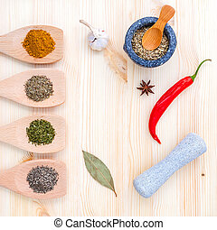 Food Cooking ingredients. Dried Spices herb bay leaves,turmeric,chili,black pepper,fennel,star anise ,garlic ,thyme and oregano with the mortar on rustic wooden background.
