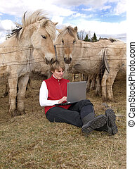 Wireless work - woman working on computer in the countryside...