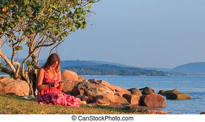 Girl in Red Sits on Beach Checks Iphone at Sunset by Rocks -...