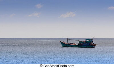 Vietnamese Fishing Boat Drifts along Sea against Horizon -...