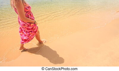 Girl in Red Long Dress Walks Barefoot along Water on Sand...