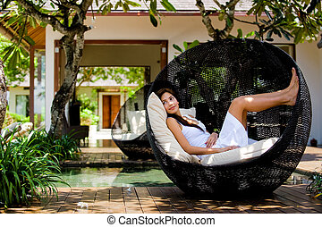 Lounging Outdoors - An attractive caucasian woman relaxing...