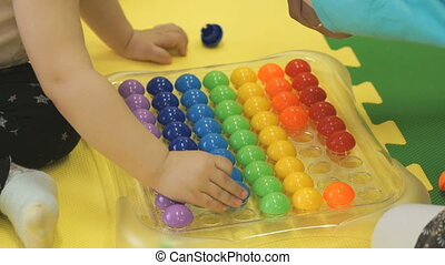 Two kids play an intelligent game with small balls - Two...