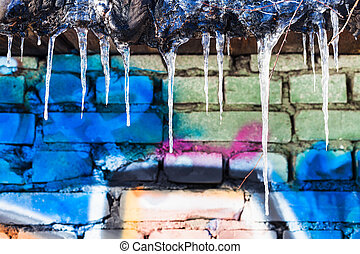 icicles on roof of shed with painted brick wall in sunny...