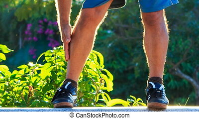 Closeup Man Does Morning Exercises Bends to Feet in Park -...
