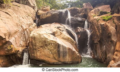 Small Waterfalls Pour into Lake among Rocks in Park - small...