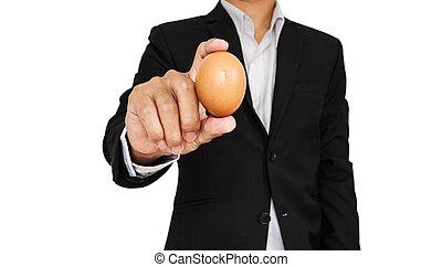 Businessman holding egg, isolated on white background
