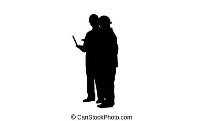 Silhouette Supervisors using laptop at construction site...