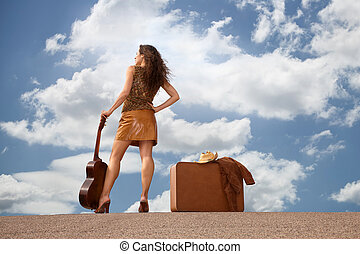Pretty woman with suitcase and guitar - Pretty brunette...