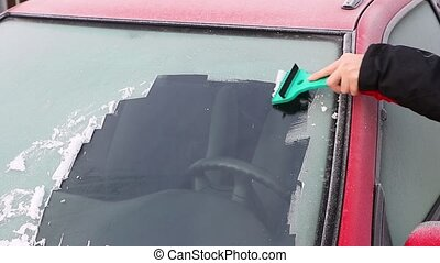 Hand is scraping ice from the windshield of the car -...