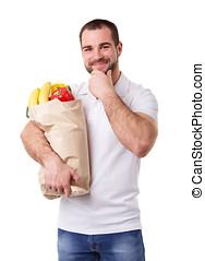 Pensive man holding paper bag full of vegetables, on white background