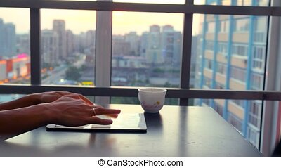 Serious young business woman using tablet sitting in a restaurant with beautiful view from window on blurred city in lights and bokeh. 4k
