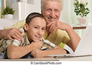 boy and grandfather with  laptop