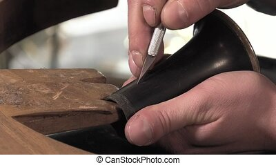 a craftsman repairing a clarinet - repairing a crack in the...