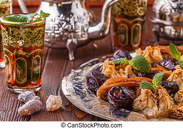 Moroccan mint tea in the traditional glasses with sweets. -...