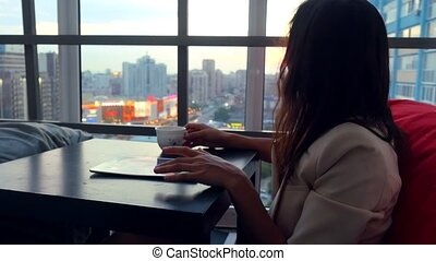 Serious young business woman using tablet drinks tea sitting...