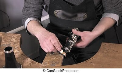 a craftsman repairing a clarinet - replacement and testing...