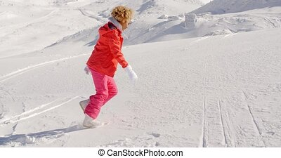 Person in snowsuit running up mountain - Single young female...