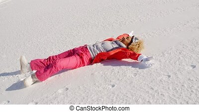Young woman enjoying the winter snow and sunshine lying on...