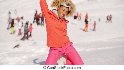 Playful young woman posing in the snow on her knees grinning...