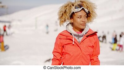 Trendy young woman at an alpine ski resort standing looking...