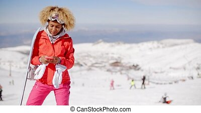Smiling skier check phone at top of slope - Single smiling...