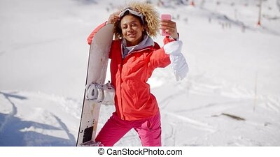 Skier taking a self portrait with phone - Happy female skier...