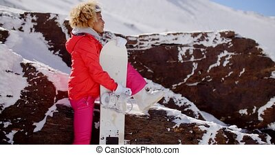 Skier leaning on rocks with snowboard - Happy young adult...